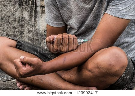 Teenager hand with heroin syringe closeup narcotic drugs addiction concept