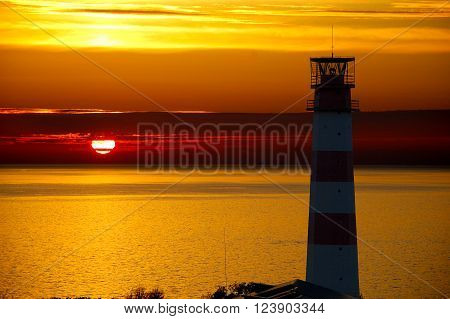 Red Lighthouse with Light Beam at Sunset. The top of a red and metallic lighthouse with light beam at sunset with clouds