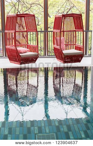 red wicker rattan chair with beige cushion and red pillow beside swimming pool