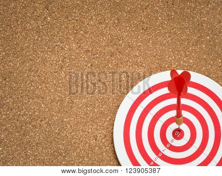 Selective focus of red dart arrow hitting target center of dartboard on cork board background. Bullseye and Dart. Success/fail business concept. Success hitting target aim goal achievement concept.