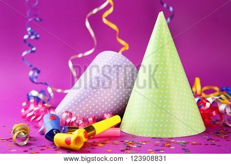 Two Birthday hats with serpentine streamer and noise makers on purple background