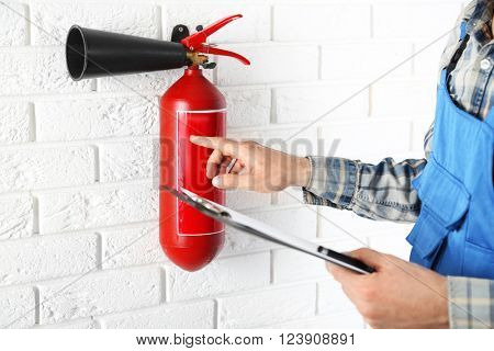 Man inspecting the fire extinguisher against white brick wall background