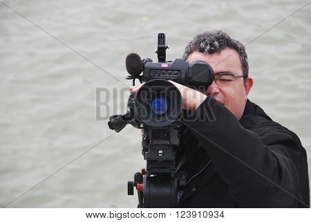 Professional videographer with camera in shooting process. Ripple water on background