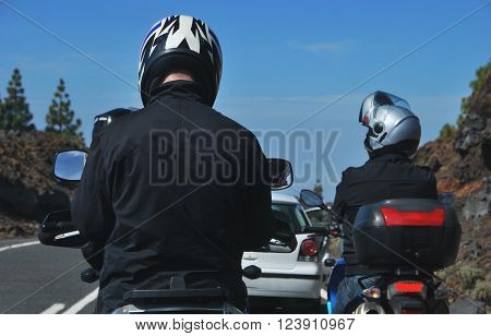 Men riding motorcycles along road against of blue sky. Traffic jam in the road