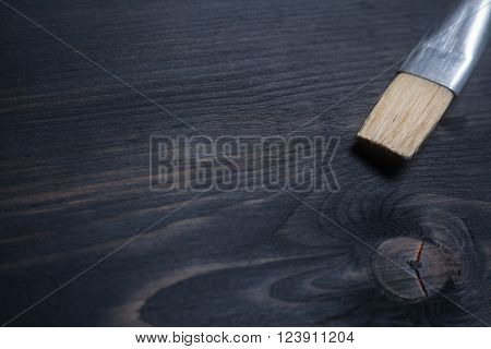 Painting brush tip on a dark wooden surface