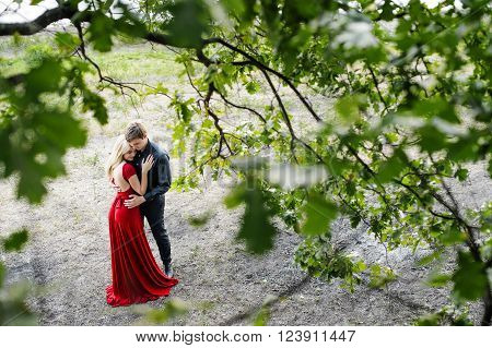 Romantic young couple embracing under a tree. Rendezvous in evening dress (top view)