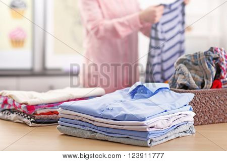 Woman putting together clothes in the room