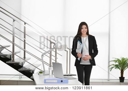 Pregnant woman at work in the office