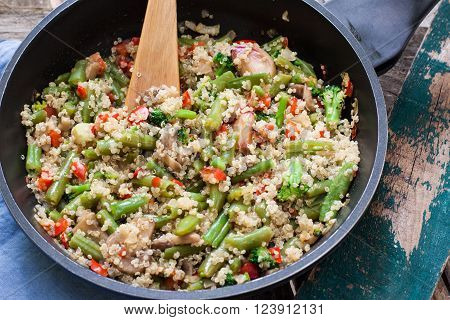 quinoa and vegetables on rustic pan with wood spoon