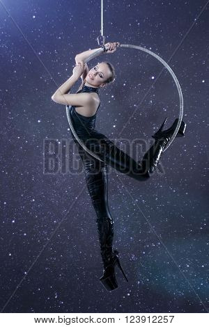 Sexy woman in latex catsuit hanging on aerial hoop at night, sensuality