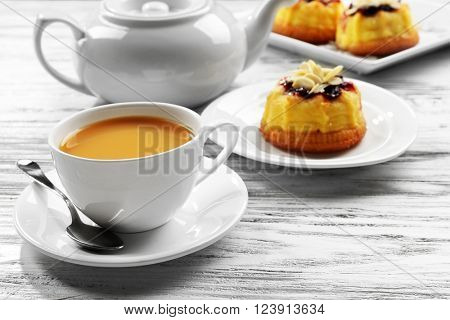 Tea with milk and cakes on wooden background