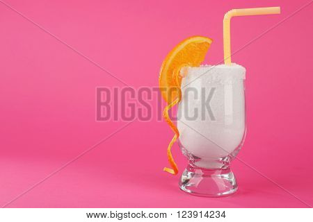 Glass with granulated sugar, cocktail straw and orange slice on pink background