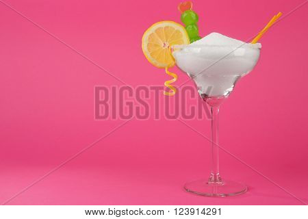 Margarita glass with granulated sugar, cocktail straws, cherries and orange slice on pink background