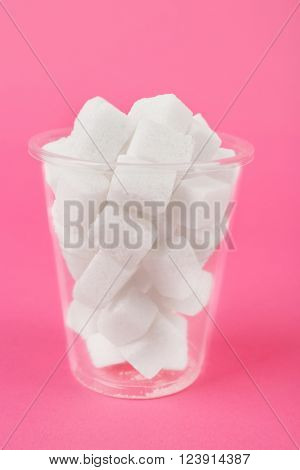 Plastic glass with with lump sugar on pink background