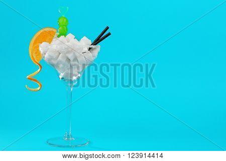 Margarita glass with lump sugar, cocktail straws, cherries and orange slice on blue background