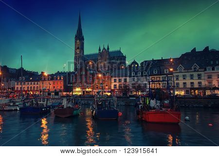 Port houses restaurants shops bars pubs and Cathedral at night in Cobh Ireland. Famous tourist seaport town and popular touristic destination