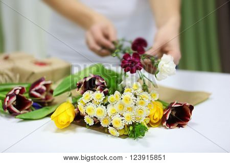Florist at work: woman making bouquet of fresh flowers.