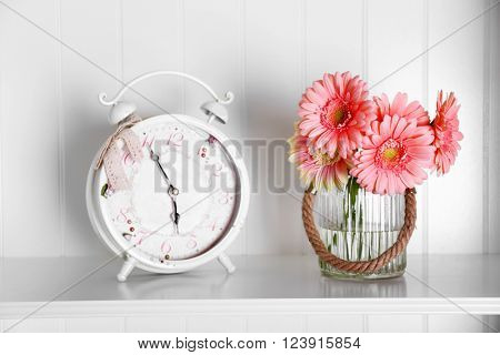 Bouquet of pink gerberas in glass vase with alarm on a shelf over white wall background