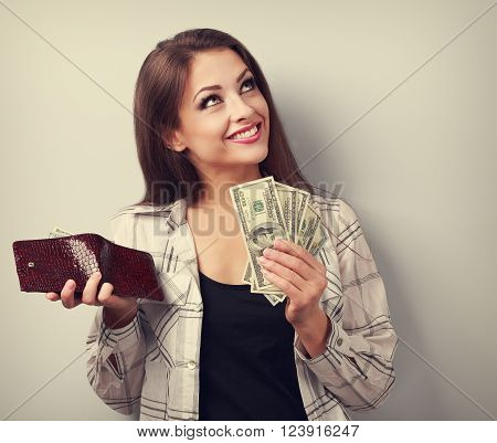 Happy smiling woman holding wallet and dollars and thinking how to spent its. Toned