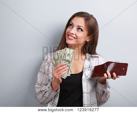 Happy smiling woman holding wallet and dollars and thinking how to spent its on blue background