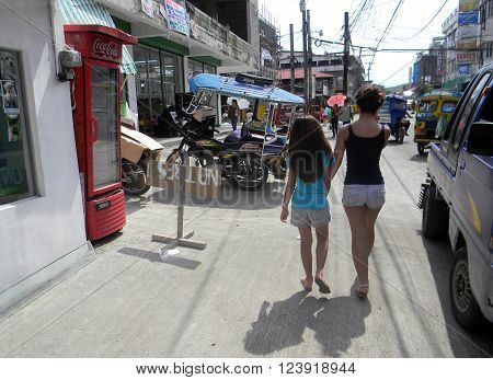 MAASIN, SOUTHERN LEYTE, PHILIPPINES / AUGUST 2, 2011: Two girls walk through downtown Maasin in Southern Leyte.