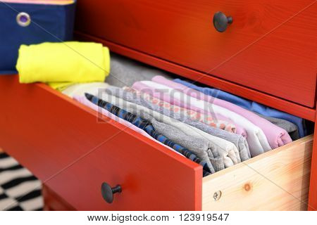 Neatly folded clothes in open drawer, close up