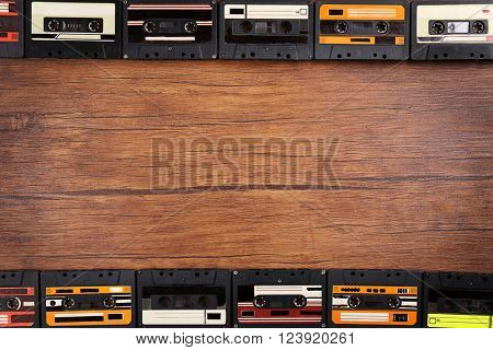 Group of audio cassettes on wooden table, copy space