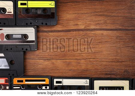 Collection of audio cassettes on wooden table, copy space