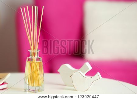 Handmade reed freshener with notebooks on white table in living room, close up