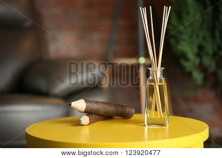 Handmade reed freshener with huge wooden pencils on yellow table in living room, close up