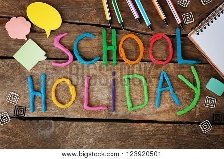 Inscription SCHOOL HOLIDAY made of colorful plasticine and stationery on wooden background