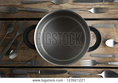 Saucepan and silver cutlery on wooden table, top view