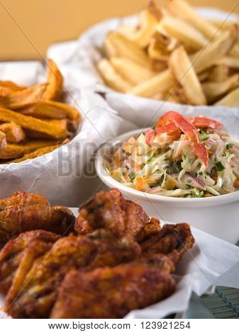 Baskets of chicken wings, french fries, and a serving of coleslaw