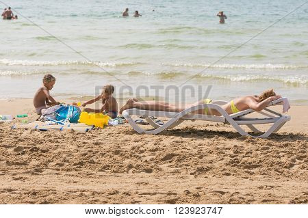 On The Beach Near The Water With A Beach Chair Sunbathing Woman Near The Children Playing In The San