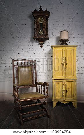 Composition of retro wooden rocking chair yellow cupboard and pendulum clock in living room