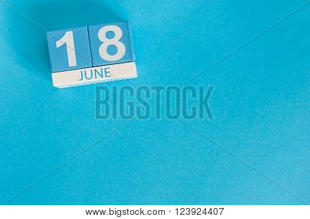 June 18th. Image of june 18 wooden color calendar on blue background. Summer day. Empty space for text.