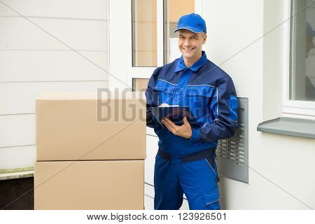 Delivery Man With Cardboard Boxes Writing On Clipboard