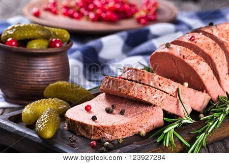 liver pate with red currants pickles and spices on a black board close-up