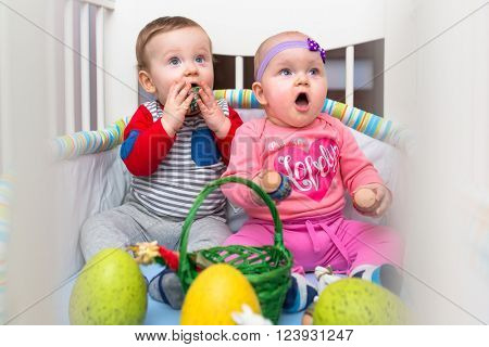Baby boy and girl twins sit in the crib with eggs for Easter