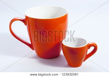 Two orange mugs one small for coffee one large for tea