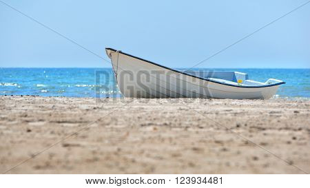 White rowing boat on white beach sand by a beautiful turquoise blue sea in summer