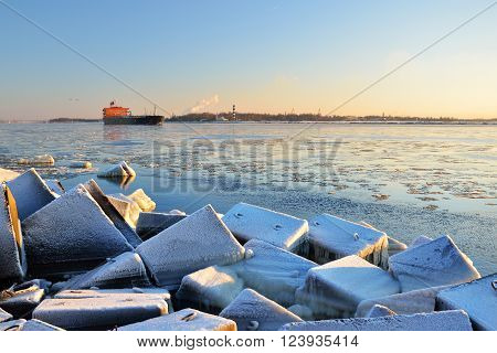Cargo ship (bulk carrier) sailing in still frozen sea with snowcovered stones in the foreground