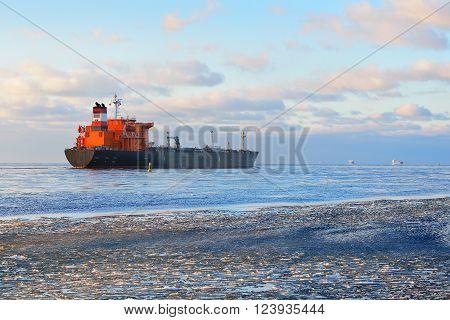 Cargo ship (bulk carrier) sailing in still frozen sea along the coastline