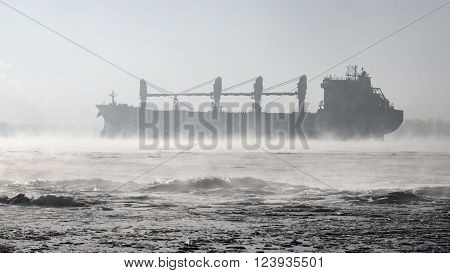 Cargo ship (bulk carrier) sailing in harsh winter conditions through a frozen sea with frosty fog
