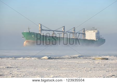Green cargo ship (bulk carrier) sailing in harsh winter conditions through a frozen sea with frosty fog