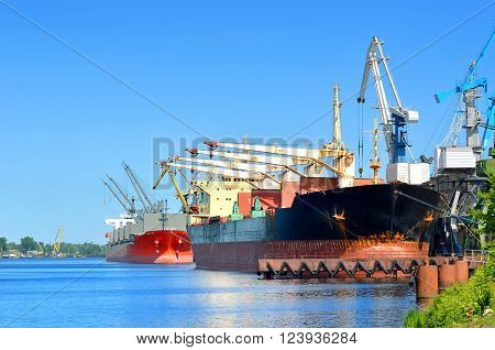 Cargo ships loading in Riga port. Industrial landscape with ships and cranes.