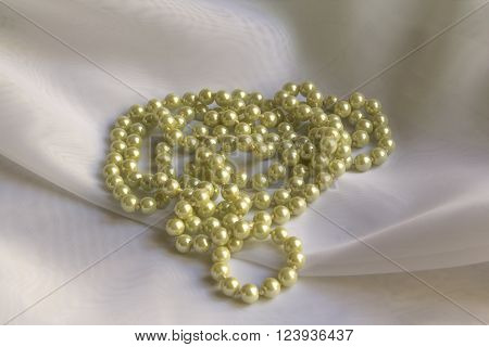Pearl necklace on white silk fabric soft