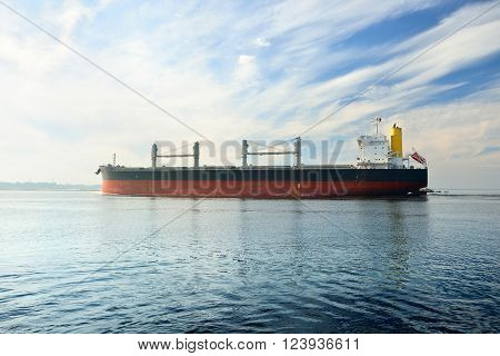 Red and black cargo ship sailing in still sea