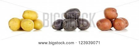 Three Piles Of Yellow, Purple And Red Fresh Little Potatoes Over A White Background