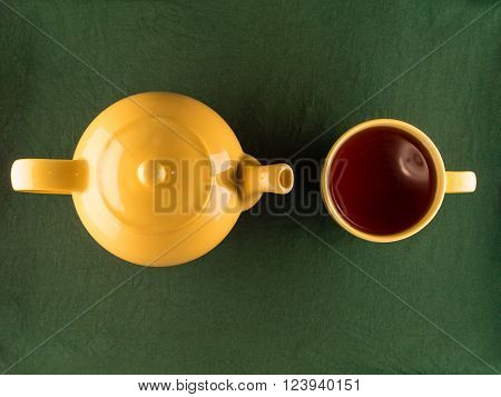 Yellow teapot and mug with tea, simple minimal top view of kitchenware with copy space